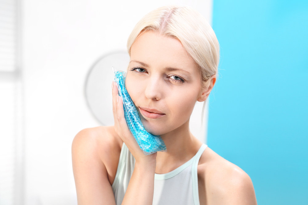 The woman puts a cold compress useful for toothache.
